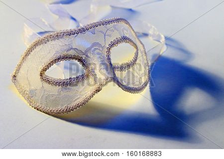 Close up of a lace carnival mask (homemade product) with blue shadow on white. Fashion background.