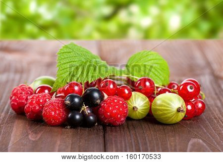 A Mixture Of Ripe Berries On A Wooden Table. Summer Still Life. Raspberries, Gooseberries, Currants