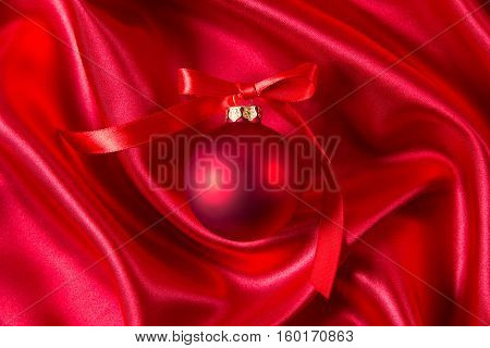 Red christmas ball with red ribbon on a red silk cloth
