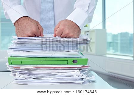 Huge heap of paperwork on workplace in office