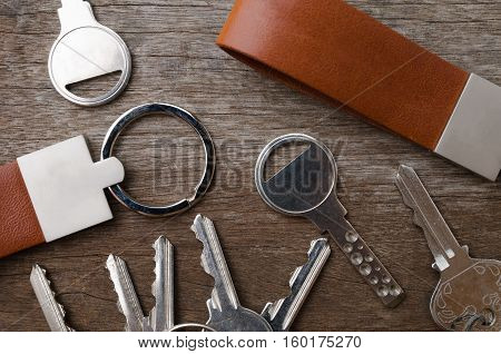 House key with leather key chain on wooden background