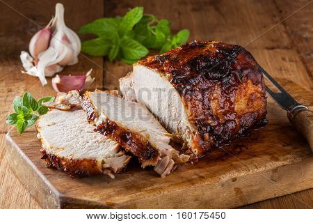 Oven roasted pork loin on a cutting board in a rustic kitchen.