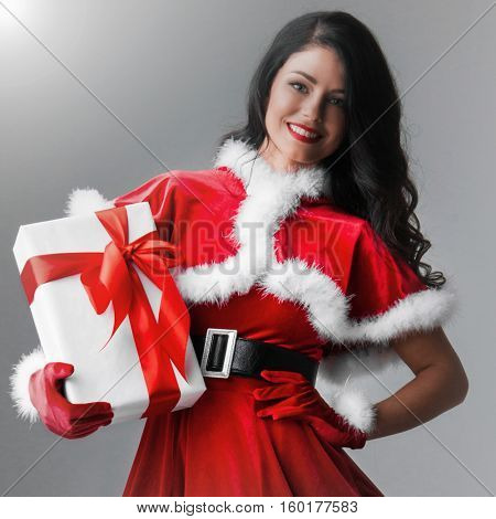 woman in red santa claus outfit holding Christmas present