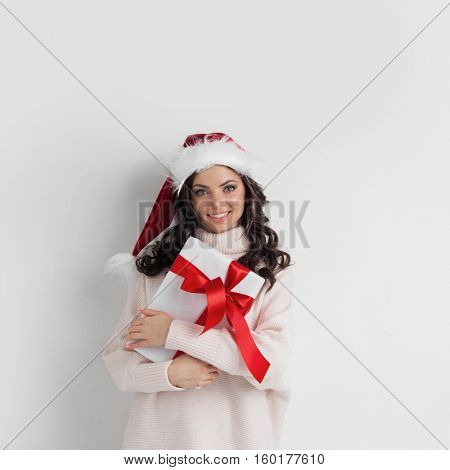 Young woman in Santa hat hug her Christmas gift