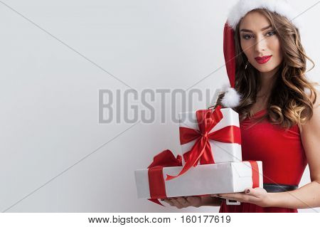Beautiful hispanic woman in red santa claus costume holding Christmas gifts