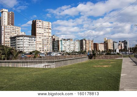 Green grass verge against city skyline on Golden mile beach front in Durban South Africa