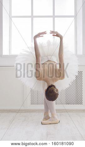 Classical Ballet dancer reverence. Beautiful graceful ballerine practice ballet positions in tutu skirt near large window in white light hall. Ballet class training, high-key soft toning.