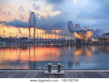 Singapore, Republic of Singapore - May 4, 2016: Panorama of Marina Bay with Artscience lotus flower museum, Flyer observation wheel and Helix bridge at sunset with decks on foreground