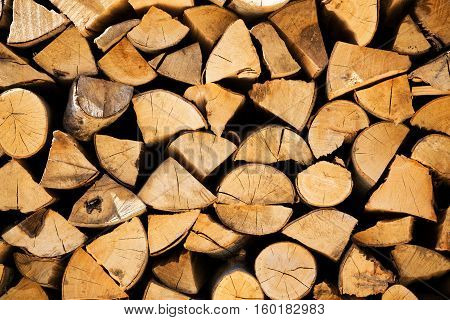 Stacked woodpile of cut and split dried logs ready to be used as natural sustainable winter fuel for household heating and energy full frame closeup texture