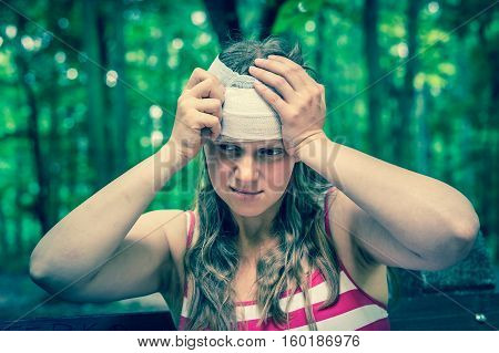 Woman Applying Bandage On Her Head After Injury In Nature