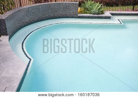Round shape water pool with bend corner close up over the waterside