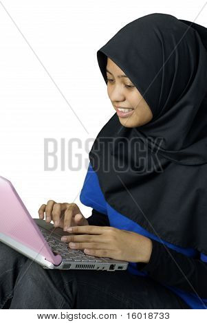 Happy asian muslim lady using laptop