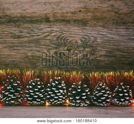 Festive Christmas background. Fir cones red tinsel and lights garland on a old barn boards. Tinted photo