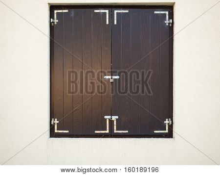 Picture of the wooden window shutters framed by a white stone wall. Brown shutters are closed with metallic padlock. Closed wooden shutters on the white background.