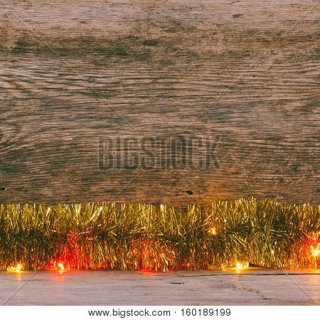 Festive Christmas background. Golden tinsel and lights garland on a old barn boards. Tinted photo