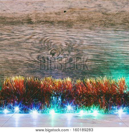 Festive Christmas background. Red tinsel and lights garland on a old barn boards. Tinted photo