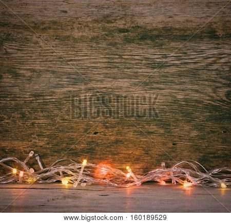Festive Christmas background. Lights garland on a old barn boards. Tinted photo