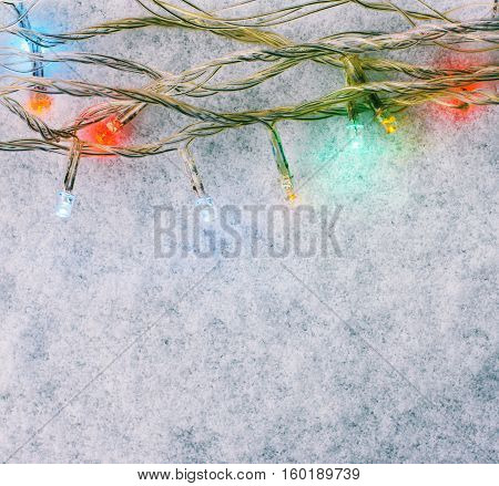 Festive Christmas background. Multicolored lights garland on the white snow