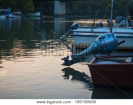 Picture of the fishing boat with outboard motor in the shallow river. Fishing boat with beige - coloured bottom anchoring on the river shore. Motor boat.