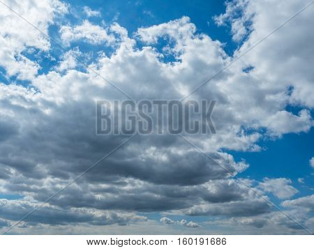 View of the cloudy sky from the ground. Picture of the blue sky with beautiful white clouds. The great foto of the white cumulus. Picture of the white cumulus moving through the blue sky.