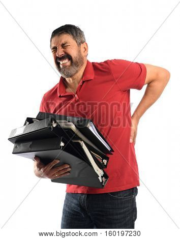 Hispanic businessman experiencing back pain while carrying binders isolated over white background