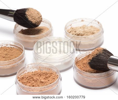 Professional make up products. Jars filled with loose cosmetic powder different shades and makeup brushes on white background