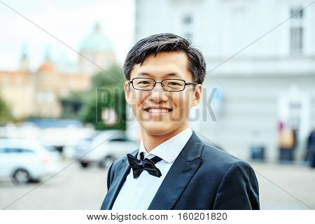 Chinese man or businessman happy handsome asian young male in eyeglasses and elegant black bow tie smiles outdoors