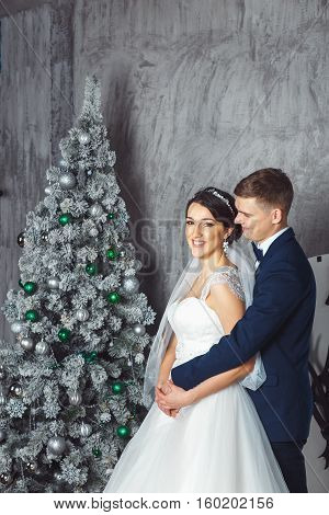 Winter Wedding .Lovers bride and groom in christmas decoration . HGroom and bride together. couple hugging. Wedding day. Beautiful bride and elegant groom walking after wedding ceremony.