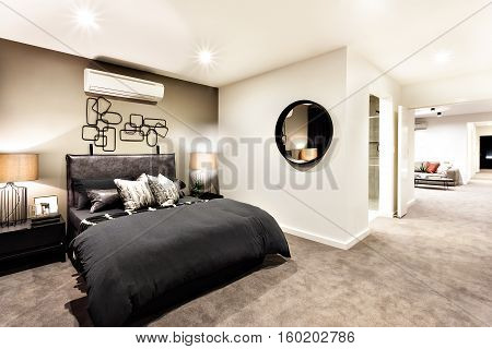 Modern bedroom with a hallway to other rooms and illuminated with night lights
