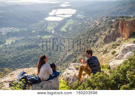 UPPER GALILEE ISRAEL - JANUARY 16: Mountain landscape in sunset light the girl and the guy sitting on boulders on a mountain top mountainous area of Upper Galilee Israel on January 16 2016