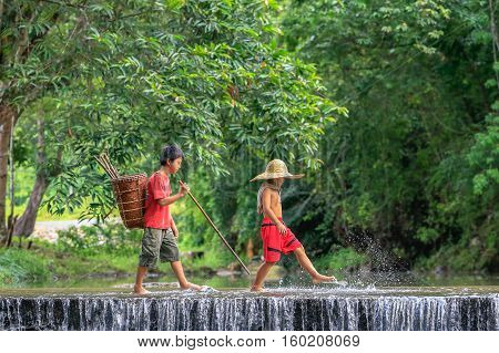 Penampang,Sabah-Oct 29,2016:Kadazandusun kids cross the river after return from jungle with carry basket at Penampang,Sabah.Kadazandusun are traditional farmers cultivating paddy rice & ravine fishing