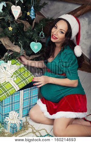 Portrait of a pregnant woman in santa dress.