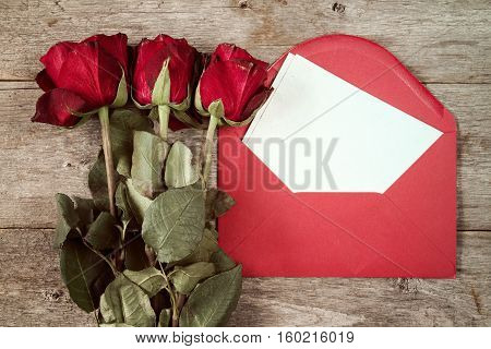 Red envelope with blank mail and old roses on wooden background