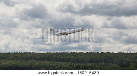 white plane flies up over the forest in the background of the cloudy sky