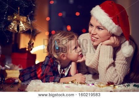 Attractive young mom in Santa hat lying on the floor with adorable child dreaming at Christmas eve. Concept of family comfort and tradition.