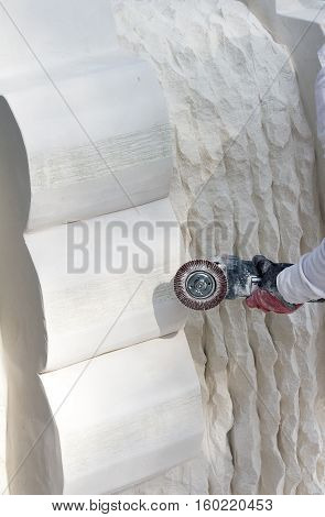 Worker polishing marble by small angle grinding machine