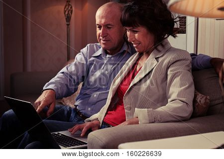 Side mid shot of a man showing something her woman on a notebook. The pair sitting on the brown couch with ornamental cushions