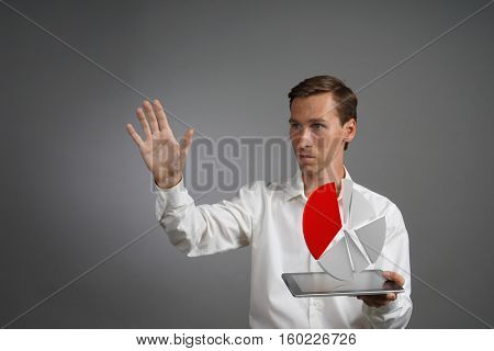 Man in white shirt working with pie chart on a tablet computer, application for budget planning or financial statistics.