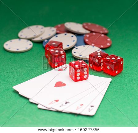 poker chips dice four aces on a green background