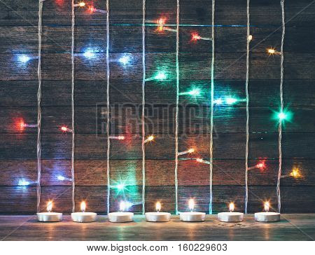 Festive Christmas new year concept. Colored lights garlands and candles on the background of old barn boards. Tinted photo