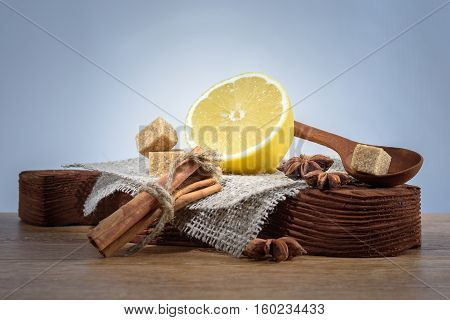 set lemon, anise, cinnamon, brown sugar on old wooden Board isolated on light background