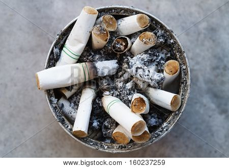Cigarette butts discarded in ashtray, Heart and lung damage.