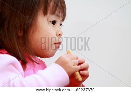 Japanese girl eating rice cracker (2 years old)