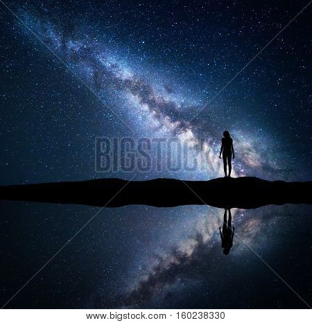 Milky Way. Night starry sky and silhouette of a standing woman on the mountain near the lake with sky reflection in water. Landscape with blue Milky Way and woman. Galaxy Universe. Space background.