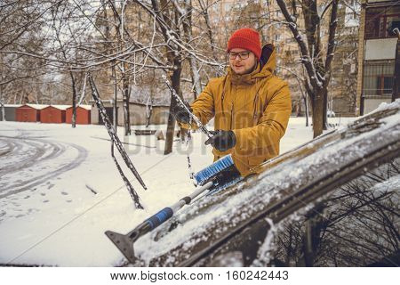 Man cleaning snow from car windshield with brush.Removing snow from car