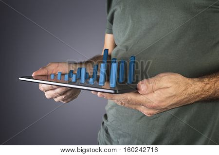 Businessman analyzing financial statistics displayed on the tablet screen. Selective focus.