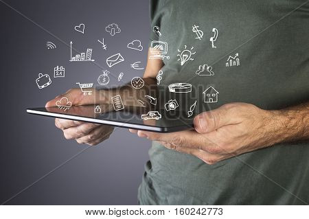 Male hand holding a modern tablet with business icons and symbols. Business technology internet and networking concept.