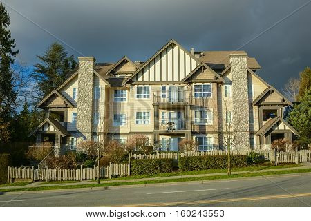 Apartment building on the slope with dark clouds background