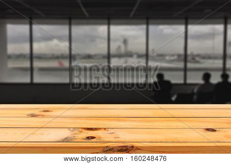 Empty wood table top with airport departure abstract blur background with bokeh lightMock up for display or montage of productBusiness presentation