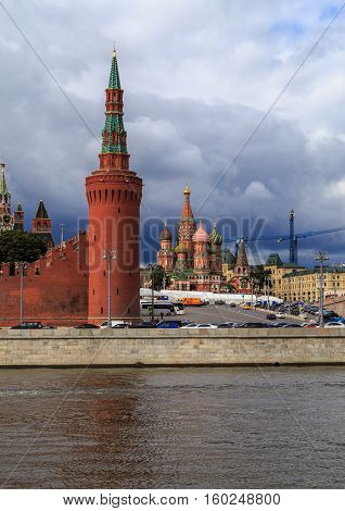 Tower of the Moscow Kremlin and St. Basil's Cathedral on the background of the cloudy sky, a view from the waterfront